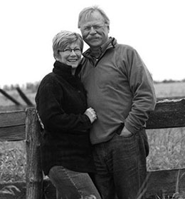 Picture of a man and woman leaning against a fence on a farm.