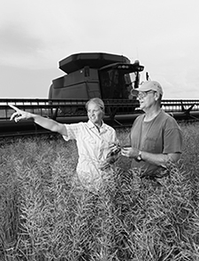 Man and woman standing in a field with combine tractor behind them.